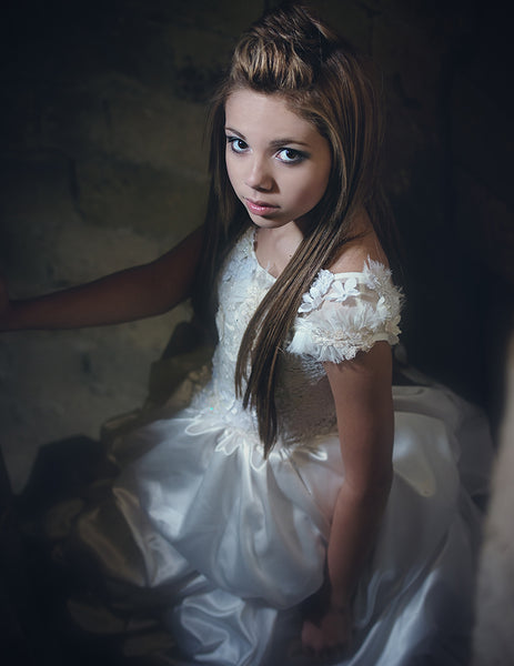 girl in a castle looking up and wearing a white dress
