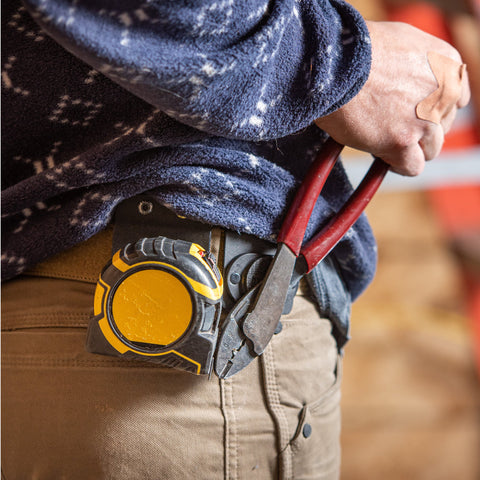 man holding a pair of pliers held onto his belt by a magnetic tool holster