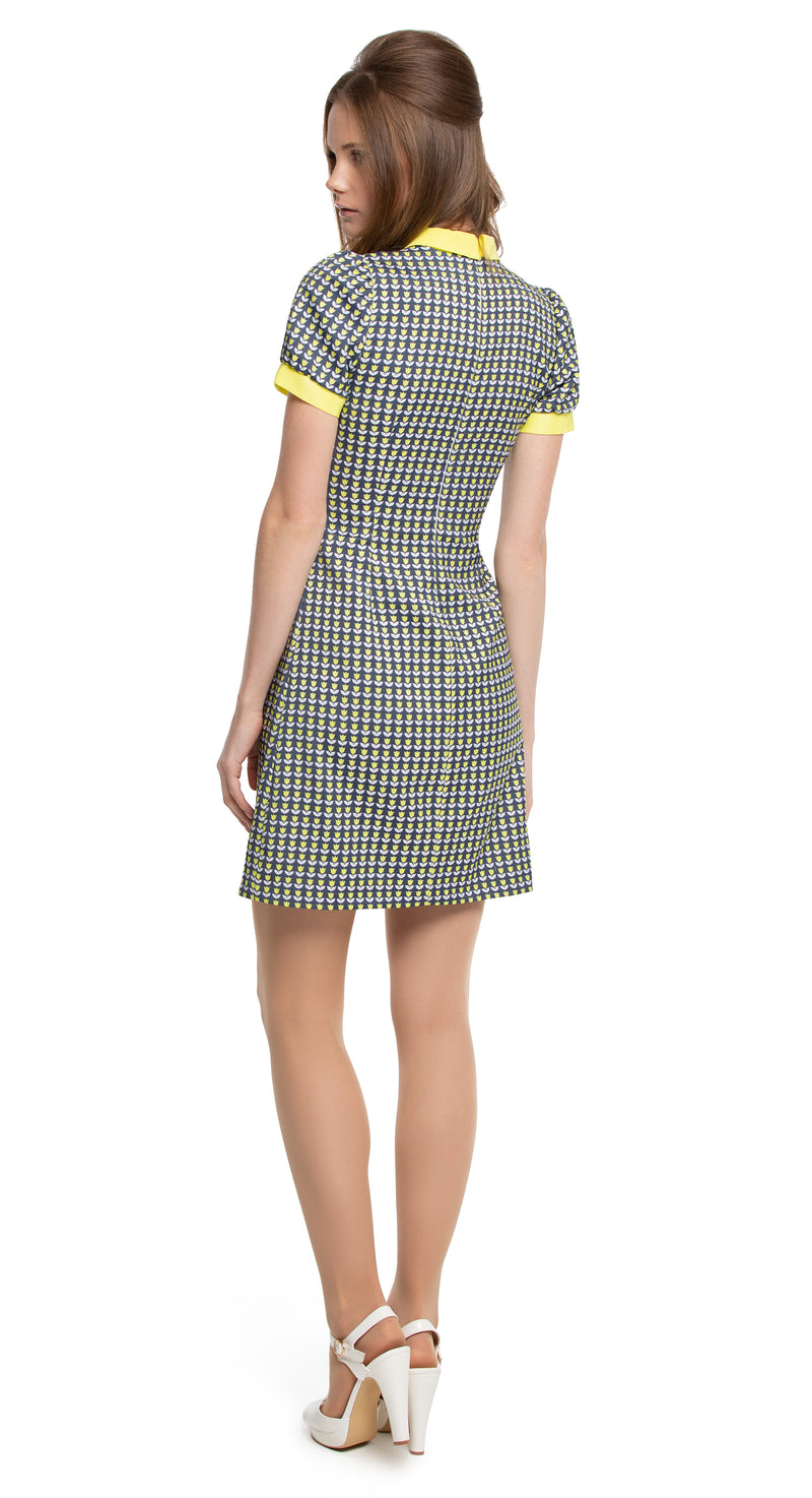 This fitted, vintage style dress, produced from a beautiful floral French weave of medium weight allows for elegance to be immediately achieved. A bright yellow tulip patterned, with matching collar, puffed sleeve and dramatic placket with four buttoned detailing on denim colour navy blue welcomes in the Spring. Worn casually and comfortably with flats daily or as an entrance maker with heels, clutch and a throw to seasonal events.