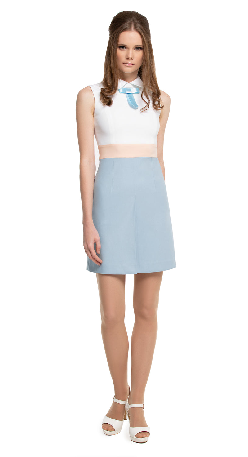 This fitted, vintage inspired tri-colour, sleeveless Spring dress has a shirt style collar and ribbon detailing. The white bodice and a dusty blue front pleat skirt are divided by a pale peach band, made entirely of Italian cotton.   Choose bespoke if preferring short sleeve or a different ribbon colour.