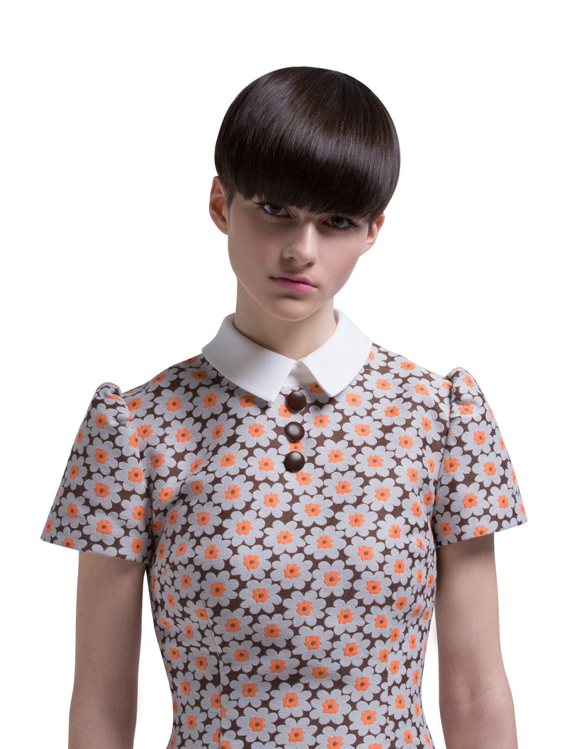 This slightly a-line 1960s mod style floral-patterned dress has slightly puffed sleeves, white collar and three detailing buttons. A style that is immediately sharp in its simplicity, allowing the French weave of Autumn colours (brown, grey, orange and white) to make this entrance maker pop.  Choose bespoke for alternative sleeve and/or dress length.