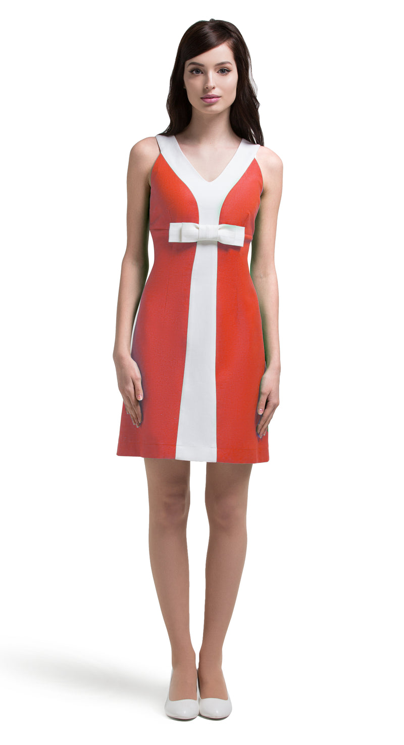 A light, comfortable and confident little entrance maker which is ideal for summer terraces, festivals and big nights out. This fun, slightly a-line dress, with a contrasting white stripe and bow is available in a lovely apple green or coral Italian cotton.  This v-neck dress has unmistakeable retro influence and immediate mod sharpness.