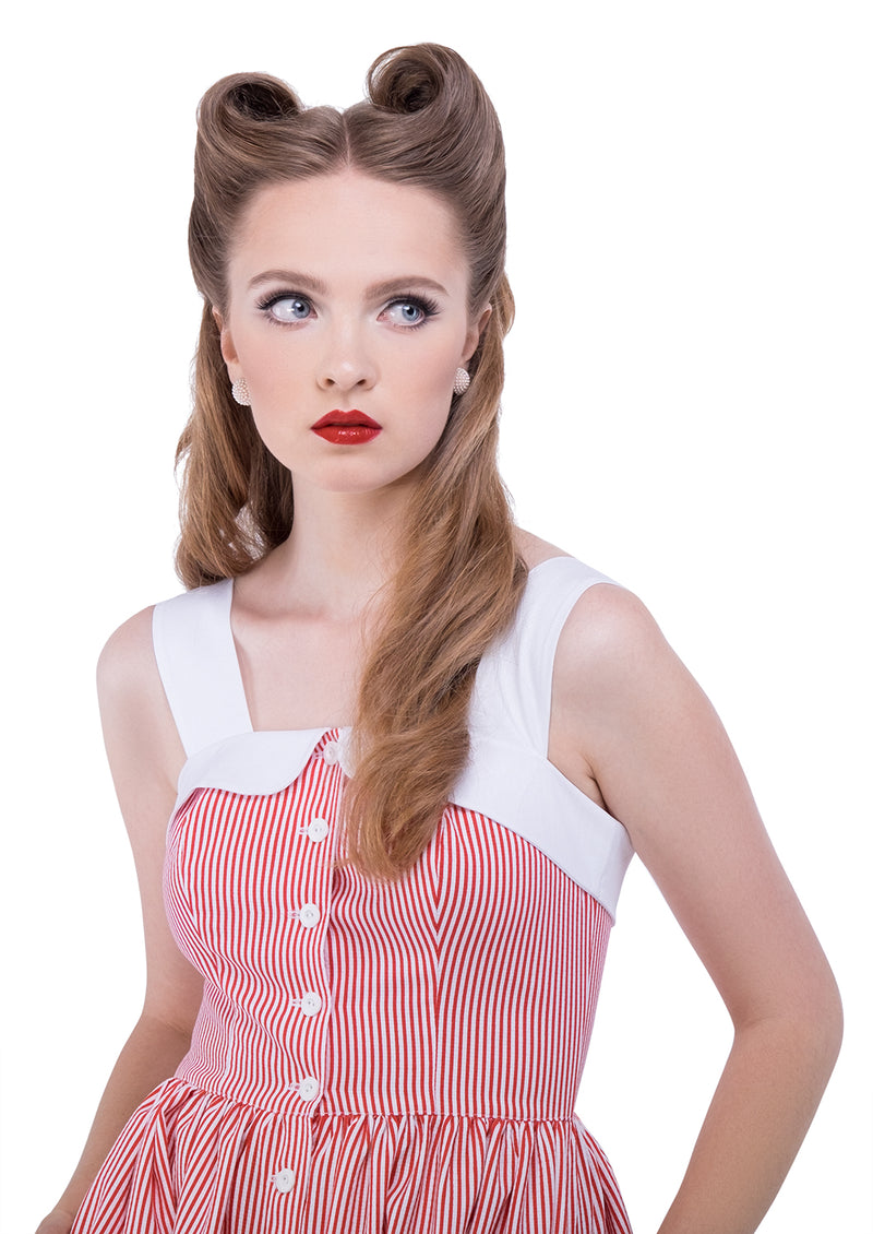 This painters shirt pinstripe 50s style dress, made of a comfortable Spanish cotton blend has medium width white shoulder straps leading to a white curved neckline. Functioning side pockets and a full run of small white shirting buttons detail this full length dress. Also available in a blue pinstripe.