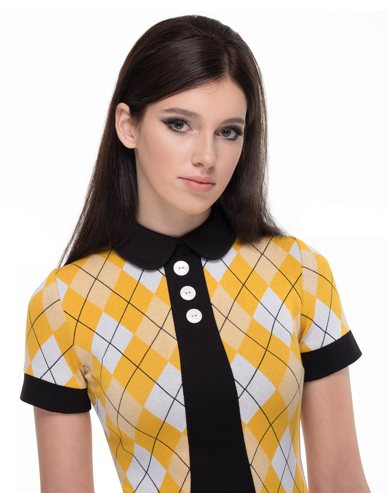Yellow, white and black pattern fitted jersey dress with black contrast and three button detail. This fitted argyle pattern Italian jersey dress is flattering and comfortable; a vintage aesthetic of sixties influence. Dressed up with heels, or down with flats, this at work or play look is immediately flattering on all silhouettes due to the jerseys generous give.