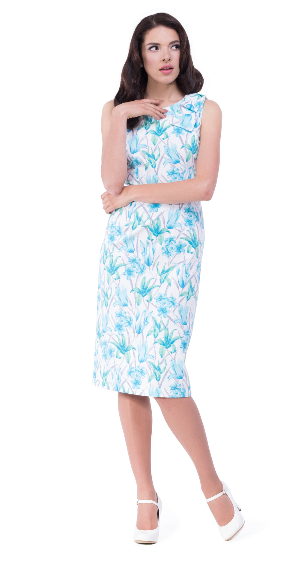 This fitted 50s style tiki floral pattern Spanish cotton blend dress has a large bow on one shoulder to compliment the simplicity of the flattering cut. A vintage style cocktail dress with an angled neckline; easy to dress up for more memorable events by way of heels and clutch. Finished with a white faux leather belt and available in as shown turquoise, or pink.
