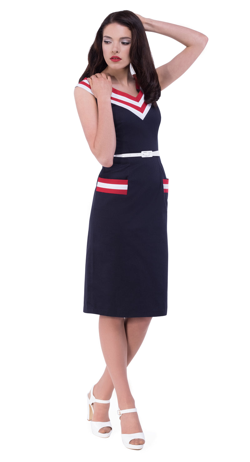 This striking 50s style full length pencil skirt with fitted bodice uses an effective v neckline made of 2 contrasting bands of colour continuing the detailing on two front functioning pockets. The dress is completed by a faux white leather belt. A very flattering dress for office or play.
