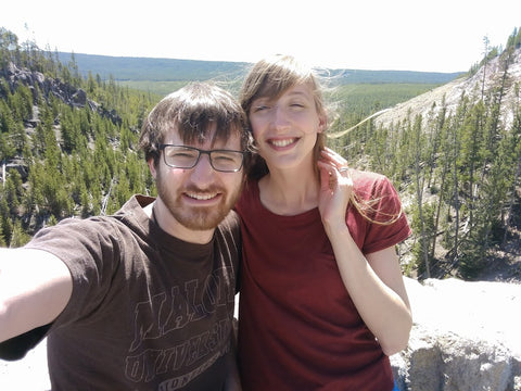 Couple in front of an overlook of pine trees