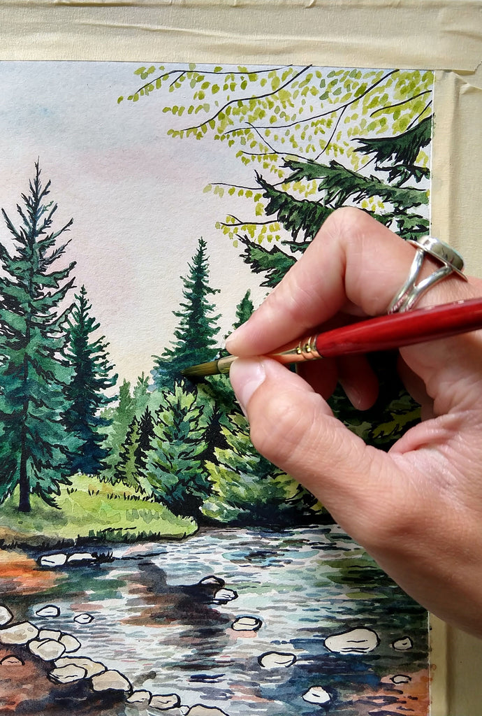 Hand holding a paint brush and painting a pine tree