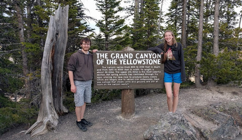 Couple standing beside a sign at Yellowstone Canyon