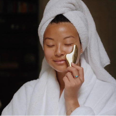Female with white bath robe and hair towel smiling with Darcase gua sha