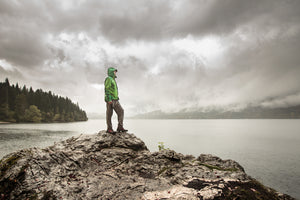 A hiker in full rain gear looks out over a lake in rainy conditions.