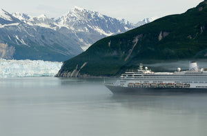 An Alaska cruise ship passes by a glacier backed by snow-capped mountains.
