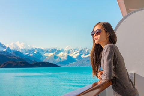 A woman on an Alaskan cruise looks out over the water with snow-capped peaks in the background.