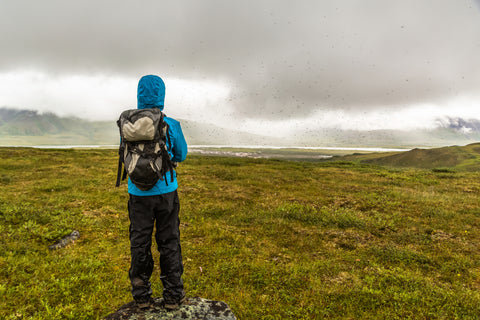 A hiker stares off into the distance during a rainstorm in Alaska.