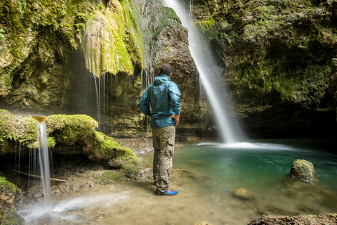 A hiker in a rain jacket stands underneath a waterfall.
