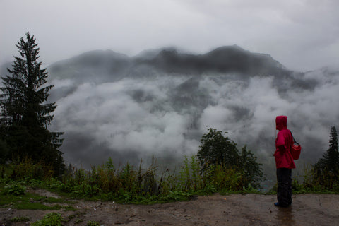 A hiker in full rain gear, including rain pants and a rain jacket stands in front of a fog-filled forest.