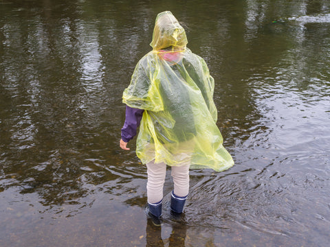A person in a poncho stands on the edge of a puddle.