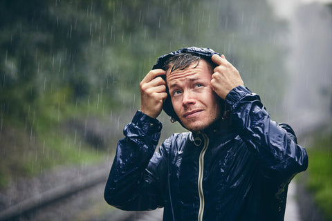 A man in a rain jacket holds his hood and watches the weather.