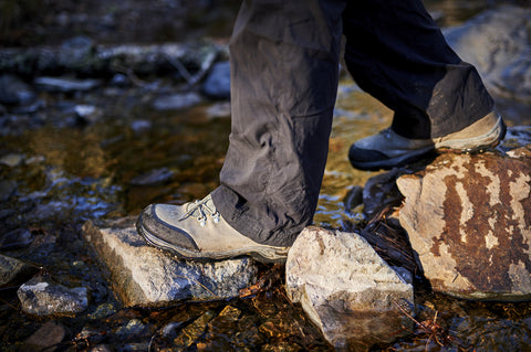 Close-up shot of full zip rain pants on a hiker crossing a stream.