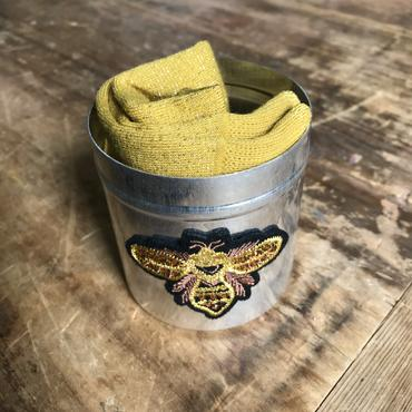 Montreal mustard socks in a large golden bee tin