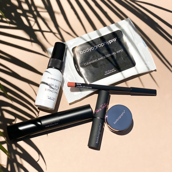 Bodyography Beauty Editor Go-To Collection: From top to bottom - Palm leaves, Mini Ready Set Go Makeup Setting Spray, 10 count Cleansing and Soothing Wipes, Lip Pencil in Pouty, Inner Glow Stick, Fabric Texture Lipstick in Chiffon, Glitter Pigment in Celestial