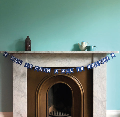all is calm paper bunting by hiya pal on blue wall with fireplace