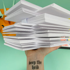 a pile of cards made from FSC accredited cardstock being held up by a hand with a tattoo that says keep the heid