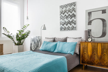 Neatly made bed with painting and nightstand
