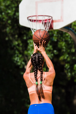 woman with hair tie braids playing basketball