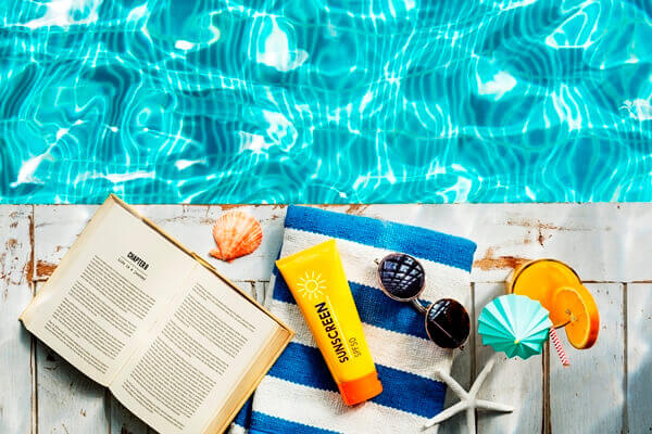Sunscreen, towel, and books beside the pool