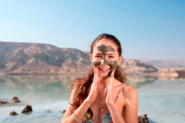 Applying mud mask to face