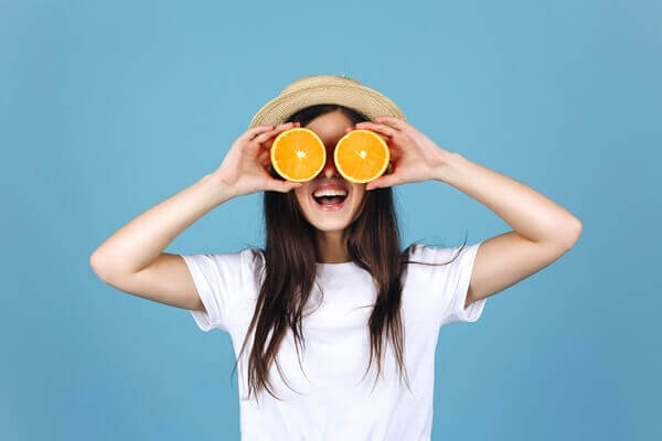 Woman holding two orange slices