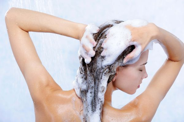 Woman with lots of bubbles on her hair while shampooing