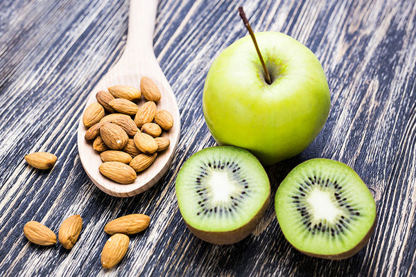 Green apple, sliced kiwi, and a spoon of almonds on a wooden table
