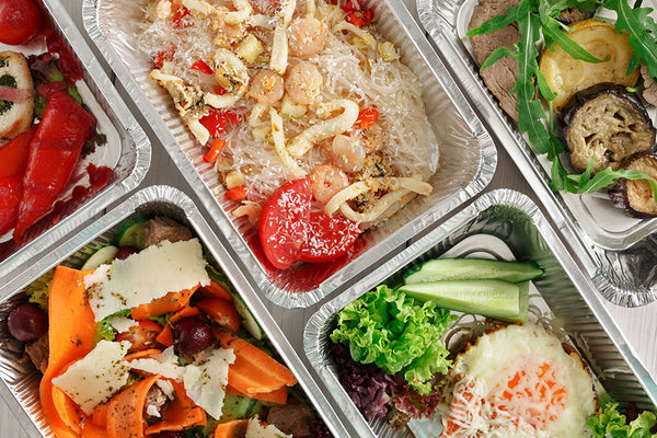 Different types of healthy food on rectangular containers