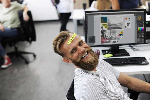 Man laughing at work, paper with 'be happy' note pasted on his forehead