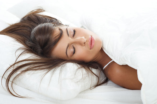 Woman sleeping on white mattress with white pillows and blanket