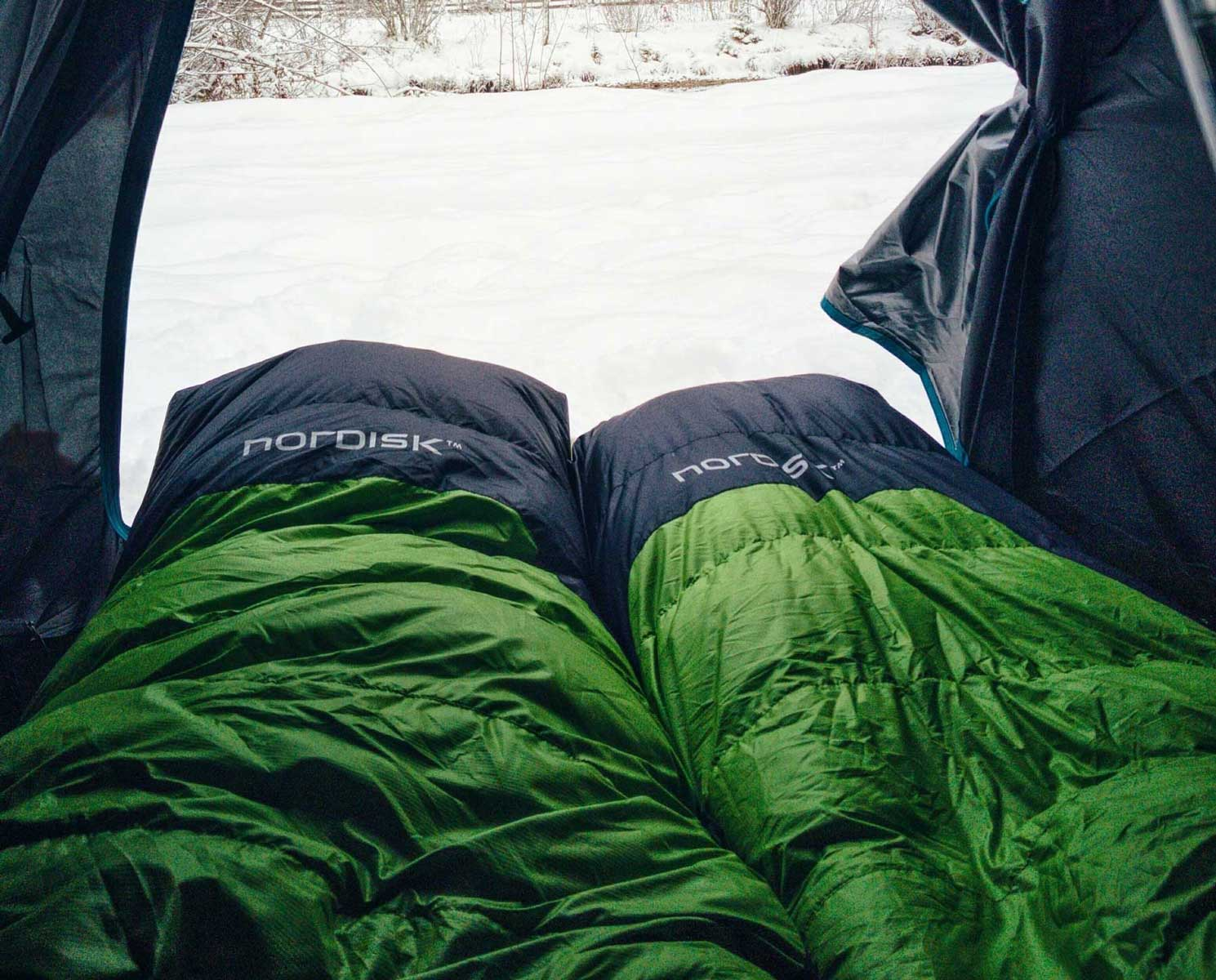 Two green sleeping bags in a tent