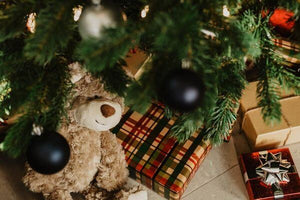 Gifts and teddy bear under Christmas tree