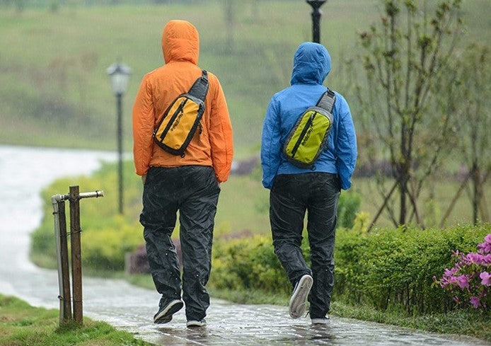 Two men walking under the rain in polyester hiking clothing