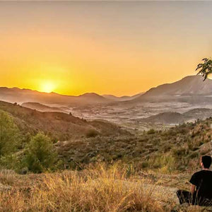 Man sitting on a hill looking at the sun