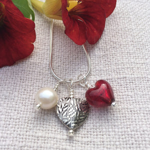 Three charm necklace in Sterling Silver with red Murano glass heart, etched heart and pearl