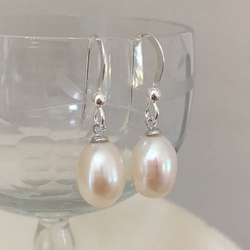 Pearl earrings with medium freshwater natural white oval pearl drops on silver hooks