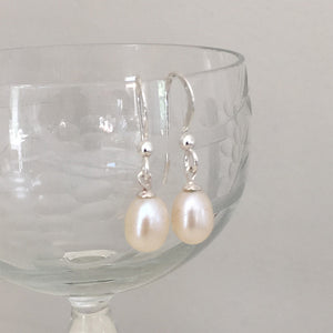 Pearl earrings with small freshwater natural white oval pearl drops on silver hooks