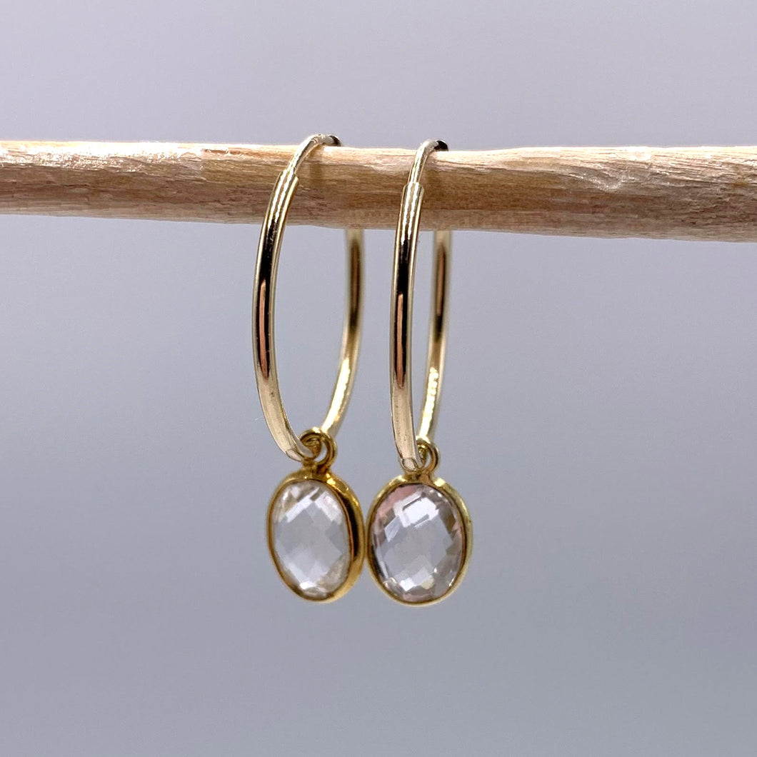 Gemstone earrings with clear quartz (rock crystal) oval crystal drops on gold medium hoops