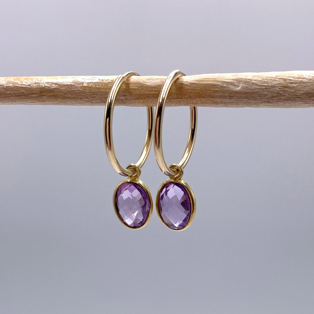 Gemstone earrings with amethyst (purple) oval crystal drops on gold small hoops