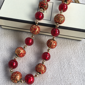 Necklace with speckled red and red Murano glass sphere beads on gold beads and clasp