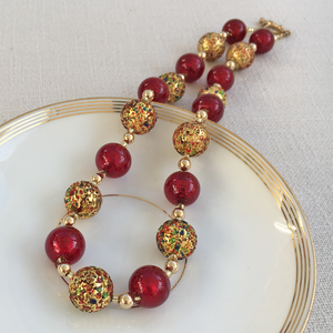 Necklace with speckled colours and red Murano glass sphere beads on gold beads and clasp