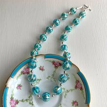 Necklace with turquoise (blue) appliqué over white gold Murano glass sphere beads on silver