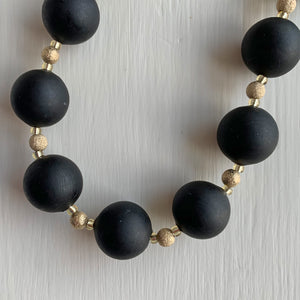 Necklace with matt black Murano glass small sphere beads on gold stardust beads and clasp